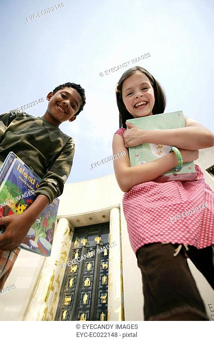 Boy and Girl walking outside with school books