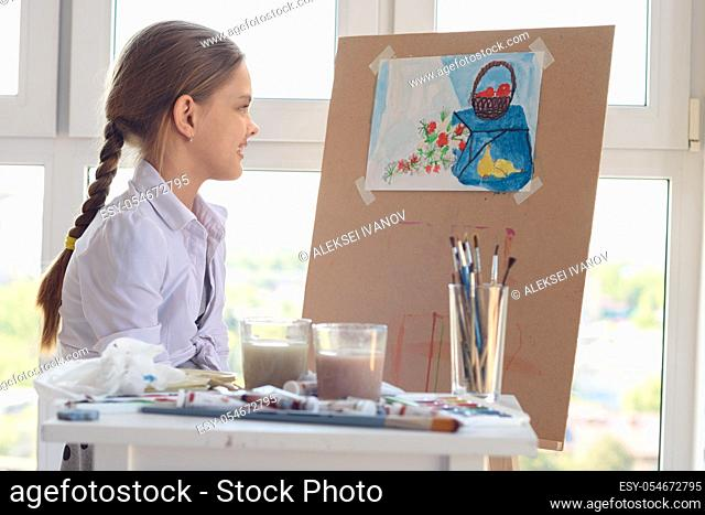 The girl happily looks at her finished drawing hanging on an easel