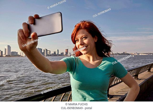 Young female tourist with long red hair taking selfie on waterfront, Manhattan, New York, USA