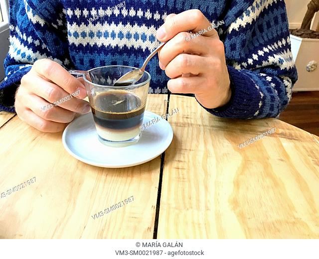 Man's hand having bombon coffee in a cafe. Close view