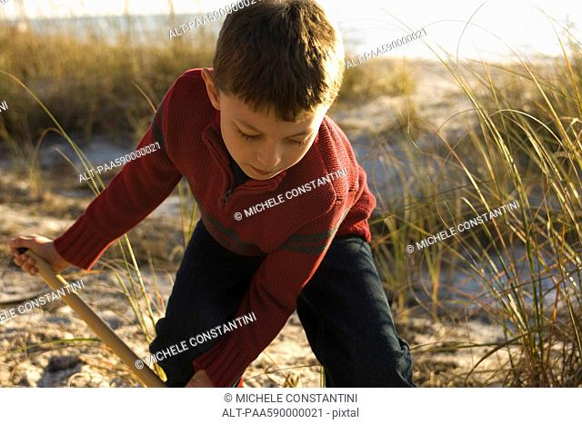 Boy digging with shovel on grassy dune, beach and sea in background