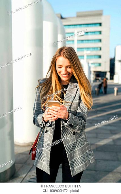 Young businesswoman with long blond hair looking at smartphone outside office building, Turin, Piemonte, Italy