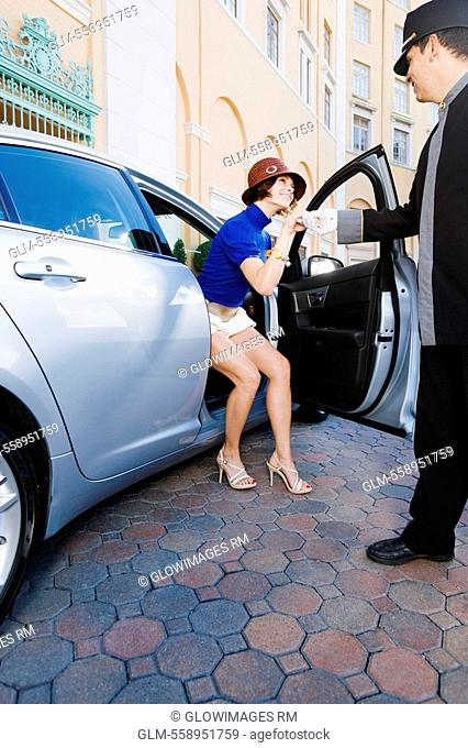 Bellhop helping out a woman from a car, Biltmore Hotel, Coral Gables, Florida, USA