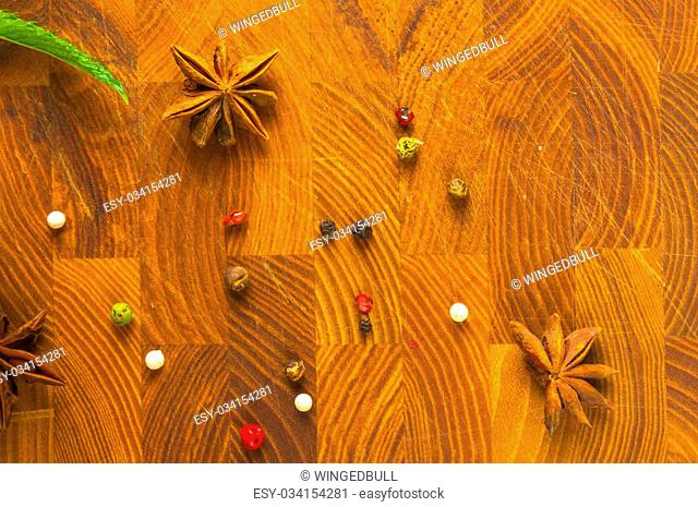 spices - a variety of allspice and star anise on wooden background