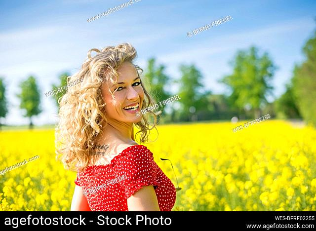 Smiling mature woman wearing red dress standing against oilseed rapes