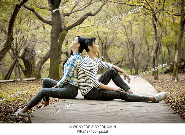 Side view of young smiling couple sitting back to back in park