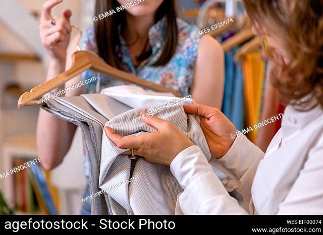Female trainee examining fabric with fashion designer