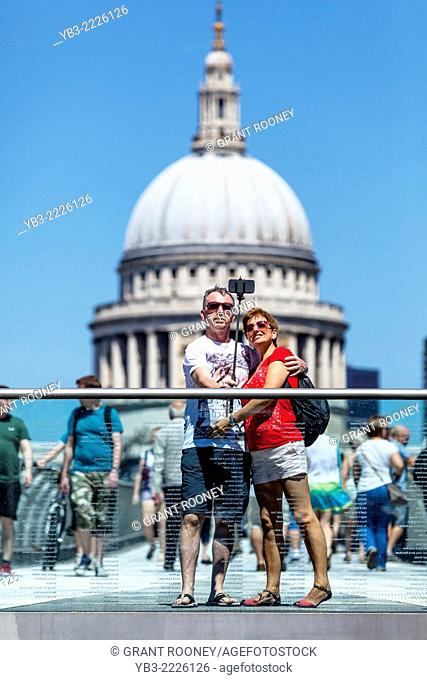 A Couple Photograph Themselves (selfie) On The Millennium Bridge With St Paul's Cathedral In The Backround, London, England