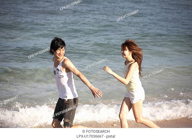 Young couple running on beach, Guam, USA
