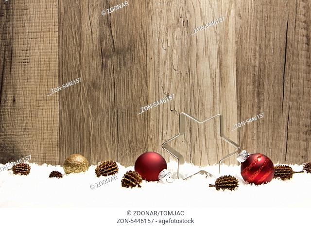 christmas decoration with wooden background, snow, christmas baubles red, poinsettia, and pine cones
