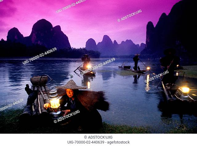 Li River cormorant fishermen on bamboo rafts lighting lanterns at dusk at Xingping Guangxi China