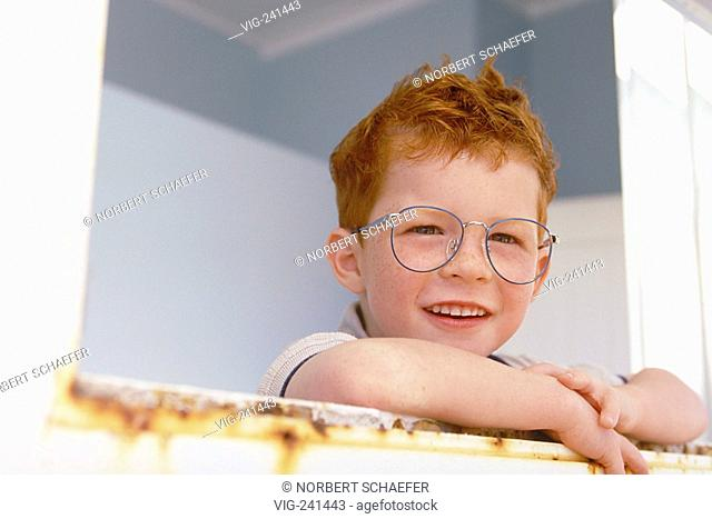 portrait, close-up, funny redheaded boy with freckles and big spectacles with blue frame, 6 years, wearing white shirt and blue trousers with flap looking...