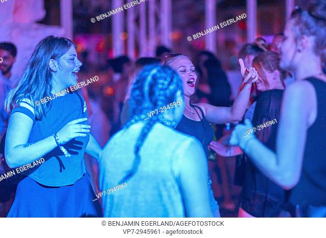group of German girls dancing at summer party at music festival. German ethnicity. At holiday destination Hersonissos, Crete, Greece
