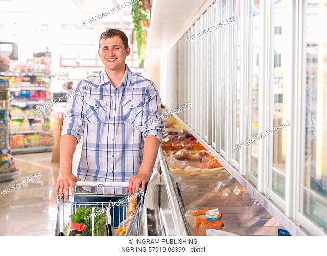 Handsome young man shopping for diary products at a grocery store or supermarket
