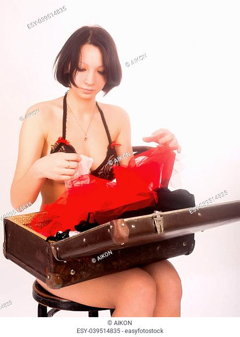 Sexy girl holding open old suitcase with underwear