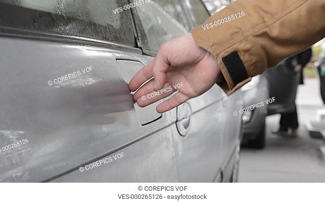 Man, refuelling his car at a petrol station