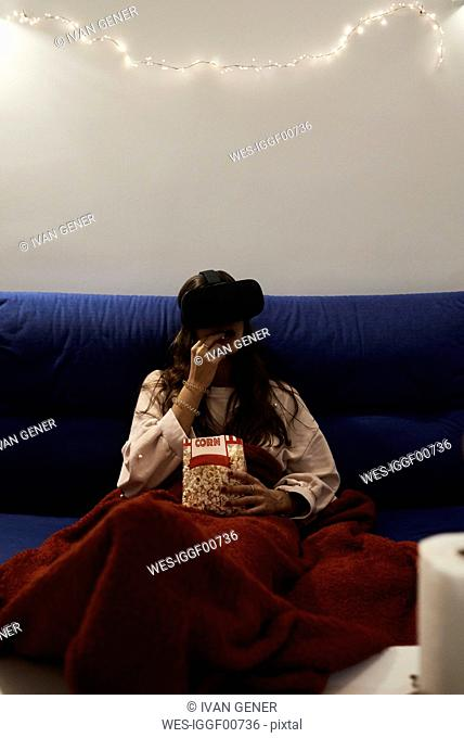 Young woman using VR headsets eating popcorn on the sofa at home at night