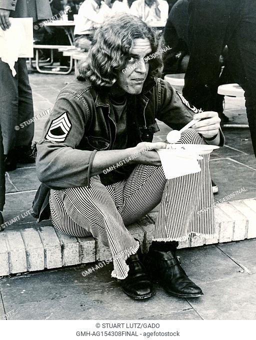 A student with long hair wearing hippie attire, including a disheveled United States Army uniform, sits on a step and eats during an anti Vietnam War student...
