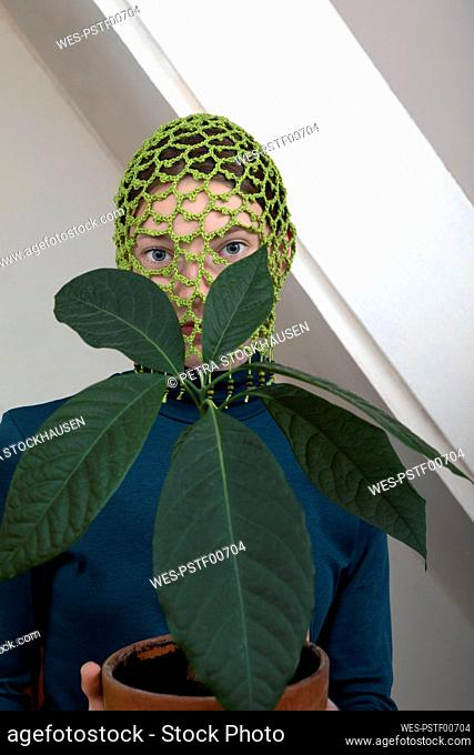 Portrait of teenage girl with potted avocado plant wearing crocheted green headdress