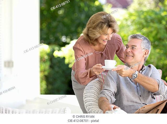 Senior woman bringing man cup of coffee on patio