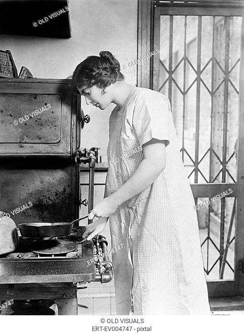 Woman cooking on stove All persons depicted are not longer living and no estate exists Supplier warranties that there will be no model release issues