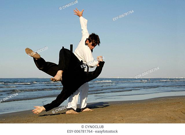 fighting of two men in taekwondo and apkido sports on the beach