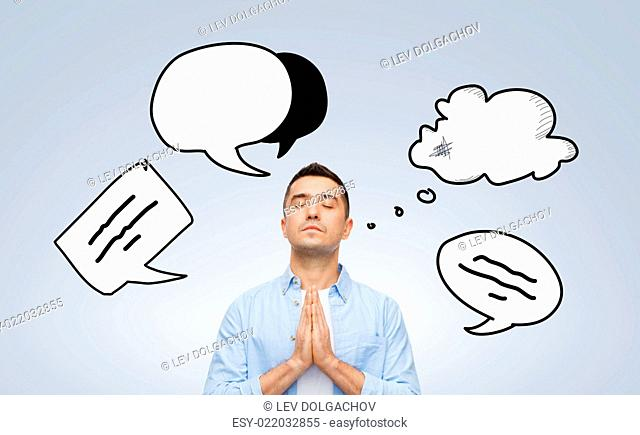 faith, religion and people concept - man with closed eyes praying to god with text bubble doodles over gray background