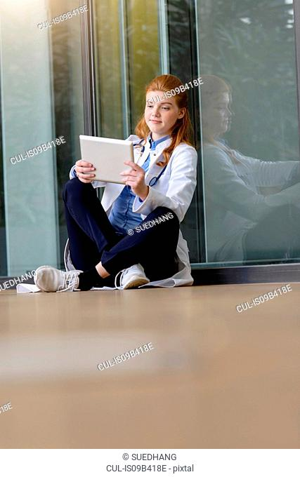 Young female doctor looking at digital tablet at hospital entrance