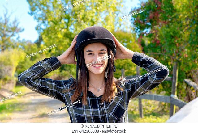 Portrait of a happy female jockey with an helmet