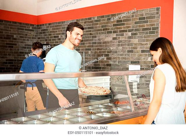Handsome young chef preparing pizza as per customer choice behind counter in pizzeria