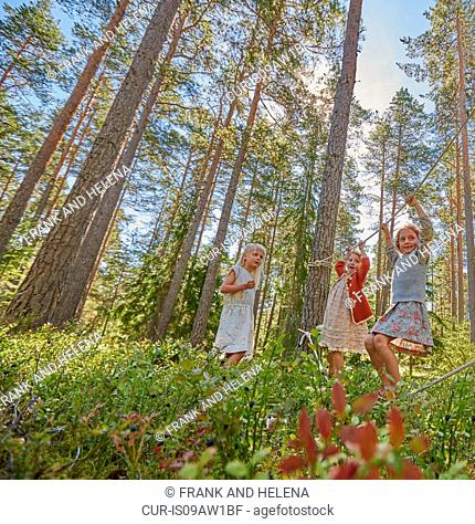 Three girls dressed in retro clothing balancing on forest ropes