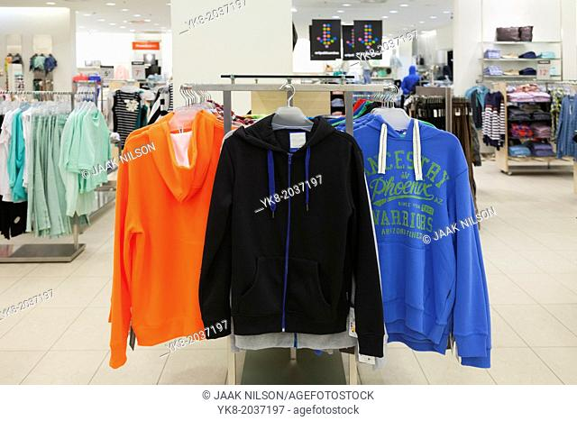 Close up of sweaters, sweatshirts on retail shop rack. Store interior