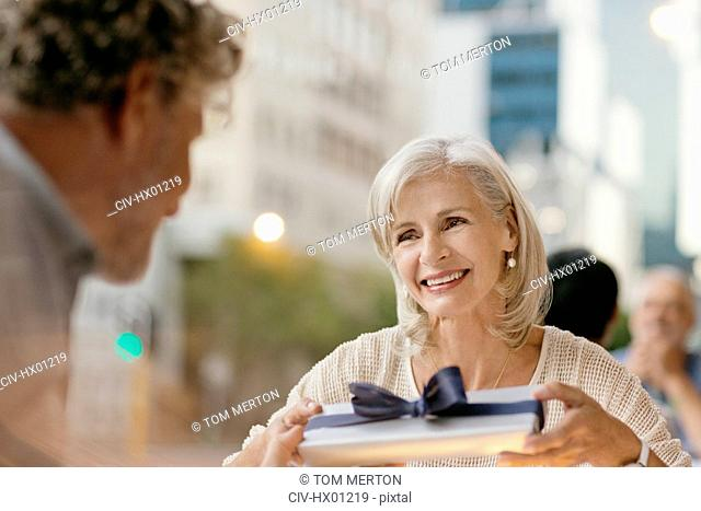 Senior woman receiving gift from husband at urban sidewalk cafe