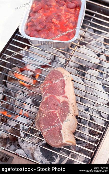 Steak on barbecue and foil dish with tomatoes and beans