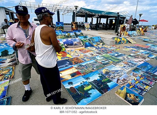 Two men at a flea market, Cuban paintings on the floor, spread out for sale, Vedado, Havana, Cuba, Caribbean