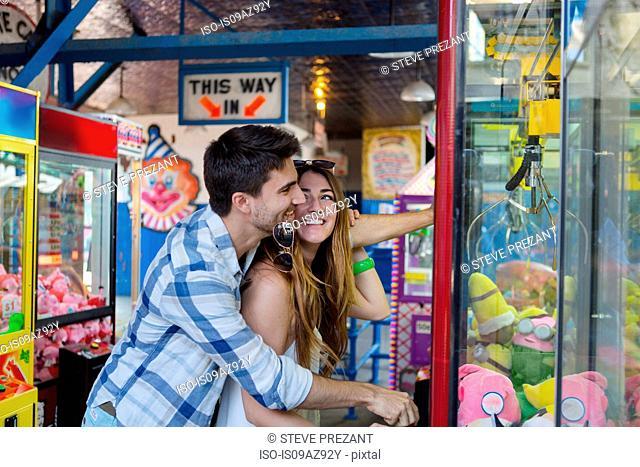 Couple at amusement park using arcade grabber, Coney island, Brooklyn, New York, USA