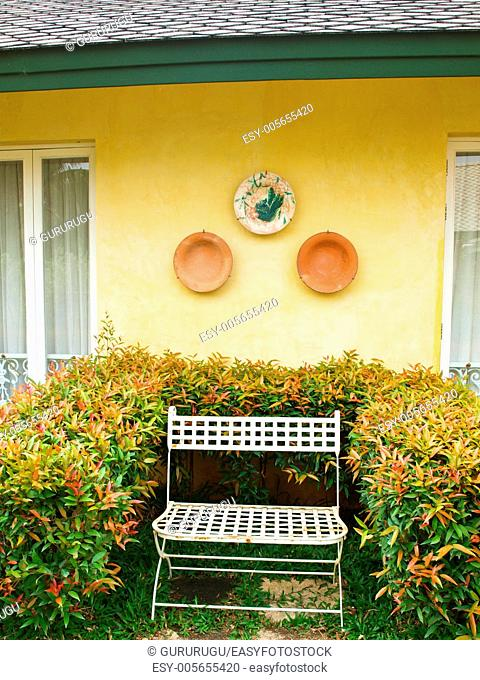 A metal bench in a garden on yellow wall background