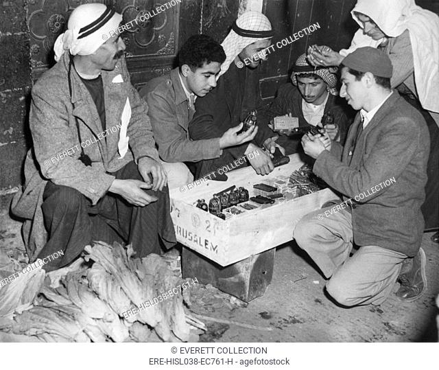 Arab Palestinians examine weapons in a Jerusalem market. Guns, bullets, and hand grenades were for sale beside vegetables on March 1, 1948