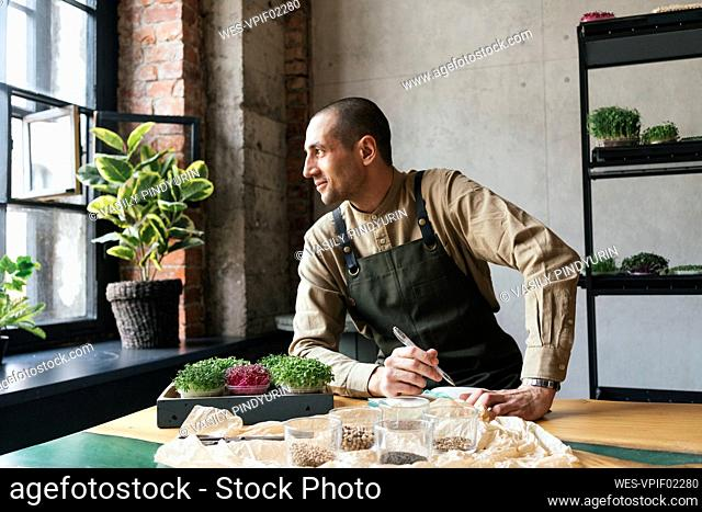 Man planting microgreens and taking notes