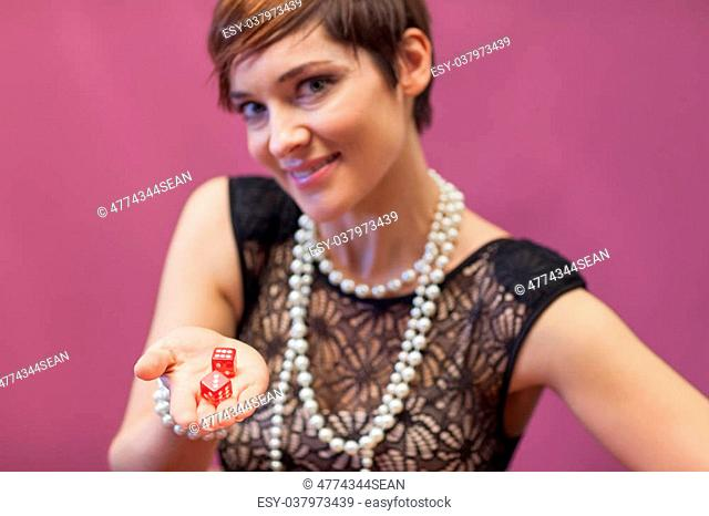 Woman in a casino holding red dices while smiling