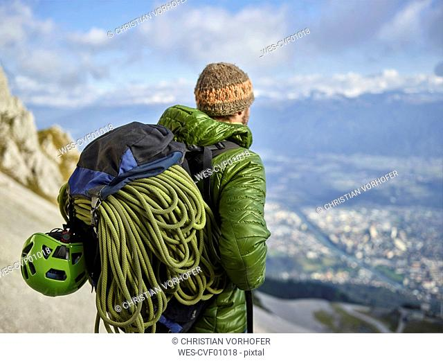 Austria, Innsbruck, Nordkette, man with rope and climbing equipment looking at view