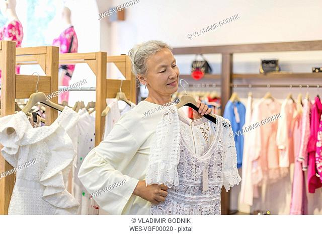 Smiling senior woman shopping for clothes in a boutique