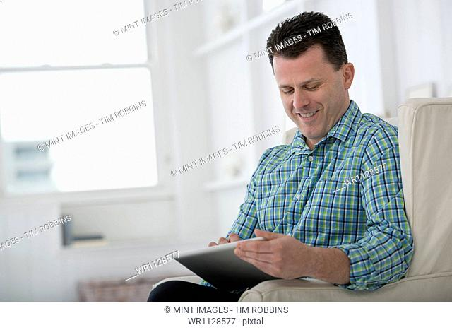 A man sitting in an armchair, using a digital tablet. A contemporary office interior