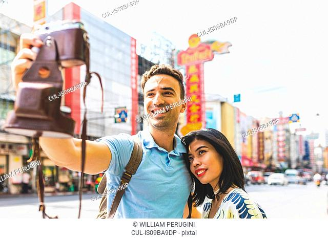Young tourist couple taking camera selfie on street, Bangkok, Thailand