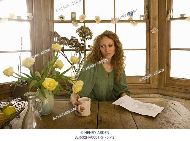 Woman drinking coffee at kitchen table
