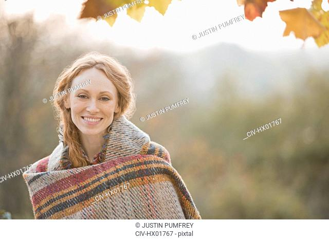 Portrait smiling woman wrapped in blanket in autumn park