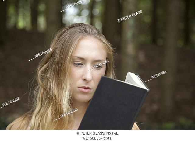 Young woman in a white dress standing by trees outdoors, reading a book