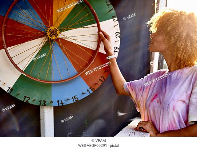 Woman turning wheel of fortune