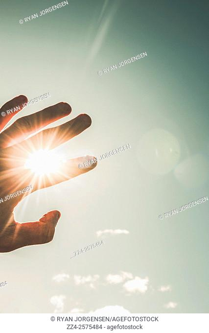 Departing human hand reaching into the light shining above in a conceptual of a passing life. Near death experiences