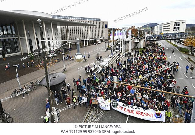 "29 November 2019, Baden-Wuerttemberg, Freiburg: On the action day of """"Fridays for Future"""" thousands of students walk through the city centre with the banner..."